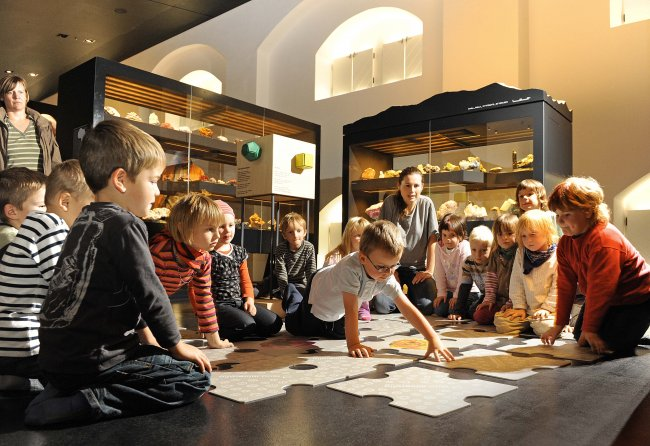 Children from a kindergarten playing a mineralogical memory with Christina Seifert (Museum's Education Service); Photo: Detlev Müller.